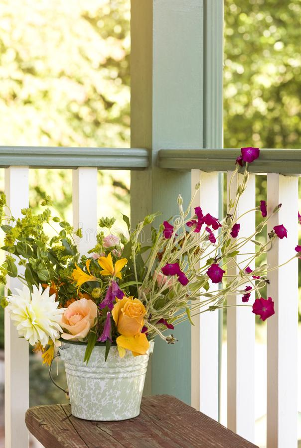 Flowers bouquet in bucket pail on front porch. Simple, country style summer home decor. Flowers bouquet in bucket pail on front porch. Simple, country style royalty free stock images