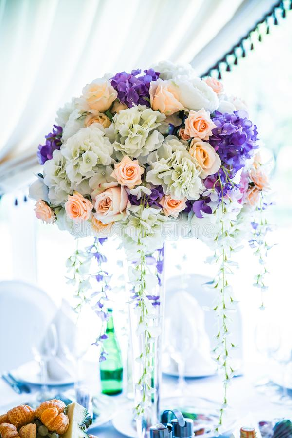 Flowers bouquet in vase on the table. In bright hall royalty free stock photography