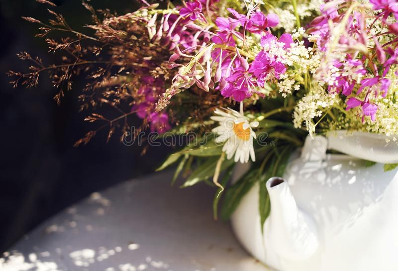 bouquet flowers close-up white kettle table sunlight stock image