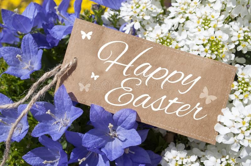 Flowers with brown card board label and happy easter. With butterflies royalty free stock photography