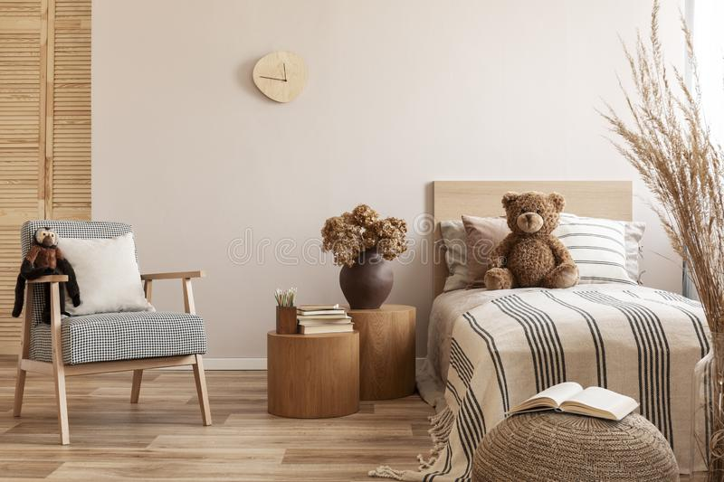 Flowers in brown vase on wooden nightstand table next to single bed with stripped bedding with teddy bear. Flowers in vase on wooden nightstand table next to stock image