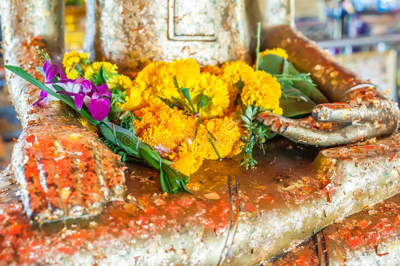 Flowers on buddha statue`s lap royalty free stock photography