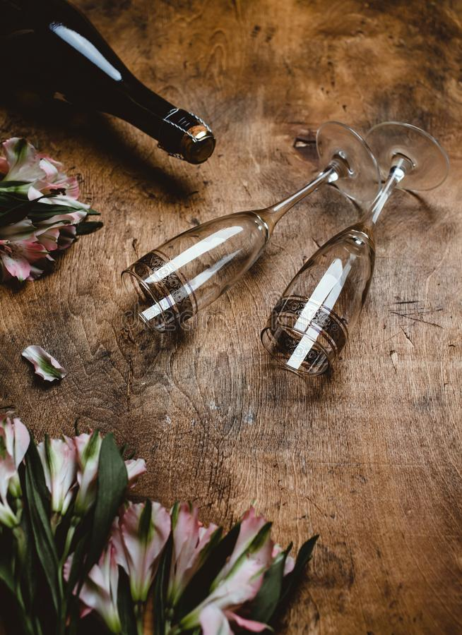 Flowers, champagne bottle and glasses. On wooden table stock image