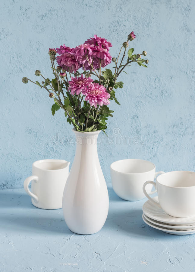 Flowers chrysanthemums in a white vase and white ceramic crockery on a blue background. royalty free stock images