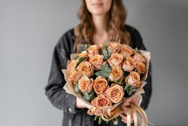 Flowers coffee color, cappuccino roses with eucalyptus. Small Beautiful bouquets in woman hand. Floral shop concept royalty free stock image