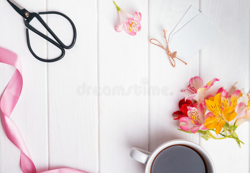 Flowers, coffee and other objects. On white wooden table, top view royalty free stock image