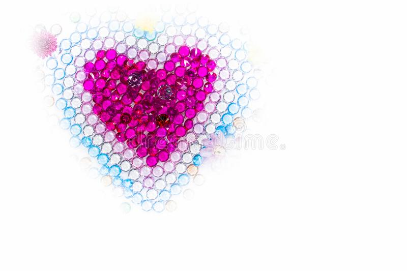 flowers and colorful polished gemstones in heart shape stock photo