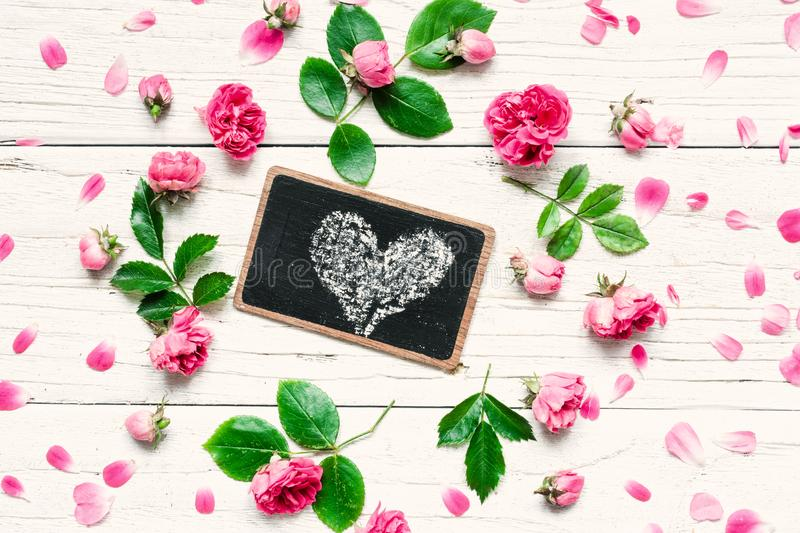 Flowers composition. Frame made of fresh rose flowers with heart on chalkboard on white wooden background. royalty free stock image