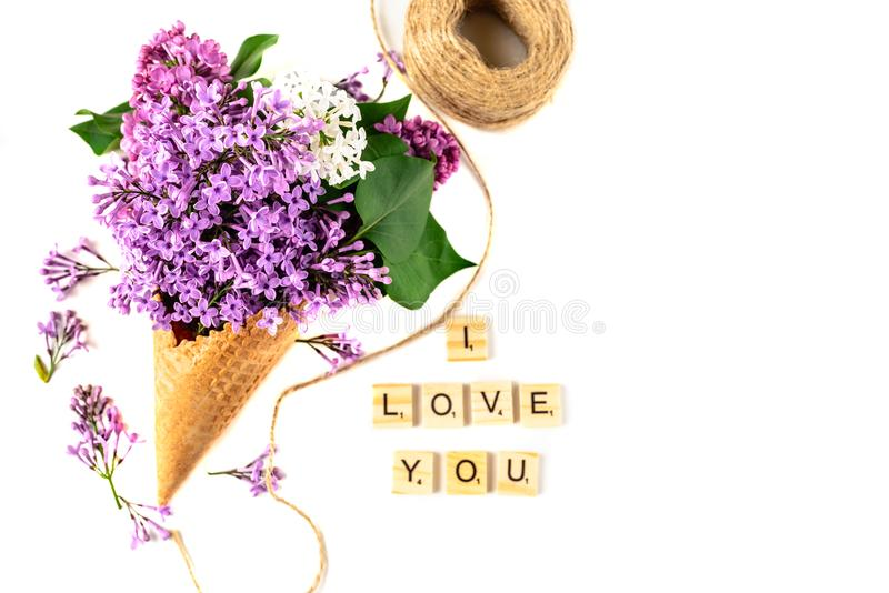 Flowers composition. Lilac in waffle cone. Flat lay, top view, copy space. Concept of proposal, love and tenderness. stock photos