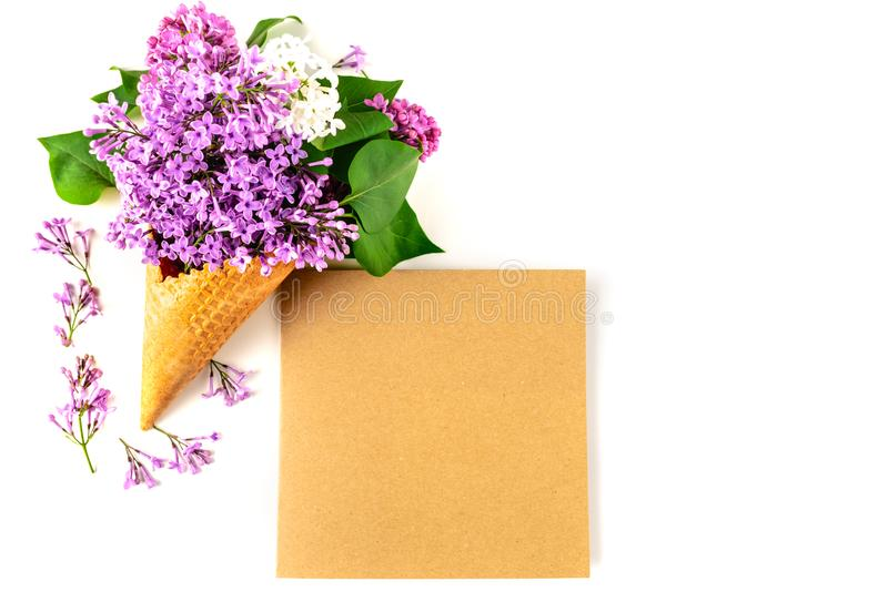 Flowers composition. Lilac in waffle cone and postcard of kraft paper on white background. Flat lay, top view, copy royalty free stock photo