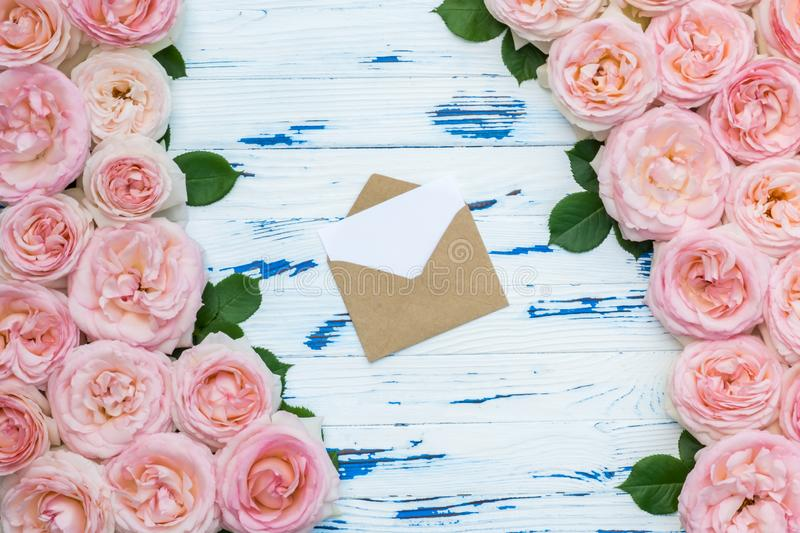 Flowers composition with open craft paper envelope in the frame made of pink roses on aged wooden background. Flat lay, top view, copy space royalty free stock images