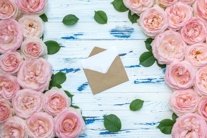 Flowers composition. Open craft paper envelope in the frame made of pink roses on aged wooden background. Flat lay, top view, copy space stock photo