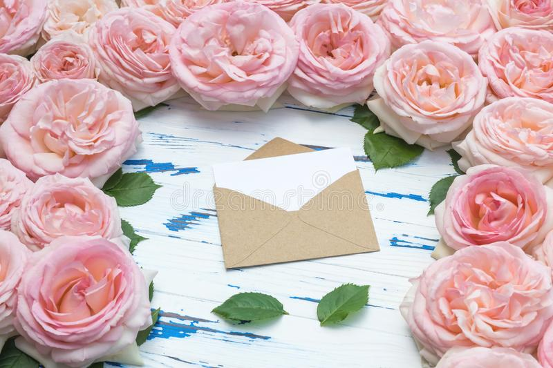Flowers composition. Open craft paper envelope and leaves in the frame made of pink roses on aged wooden table. Flat lay, top view, copy space stock photos