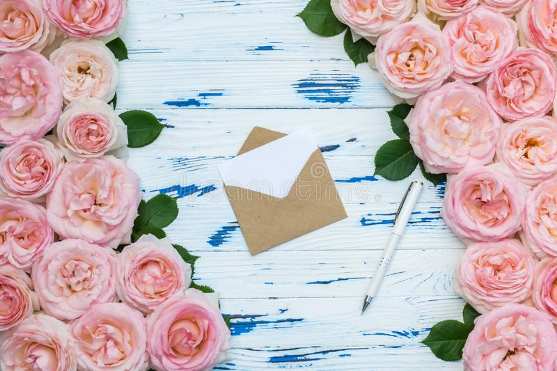 Flowers composition with open craft paper envelope and pen in the frame made of pink roses on aged wooden background. Flowers composition with open craft paper stock image