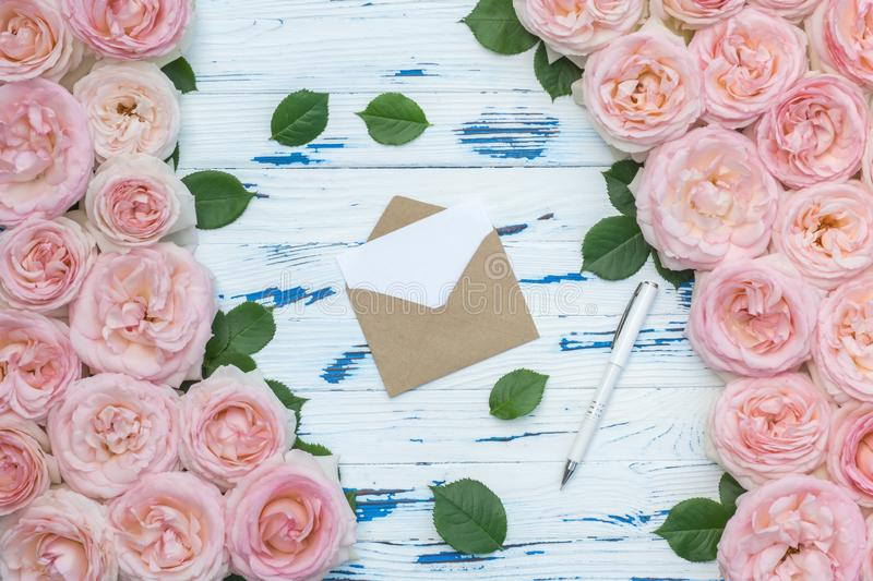Flowers composition. Open craft paper envelope and pen in the frame made of pink roses on aged wooden background. Flat lay, top view, copy space stock photography