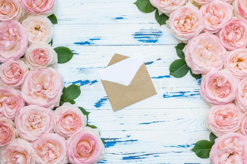 Flowers composition. Open envelope in the frame made of pink roses on aged white wooden background. Flat lay, top view, copy space royalty free stock photo