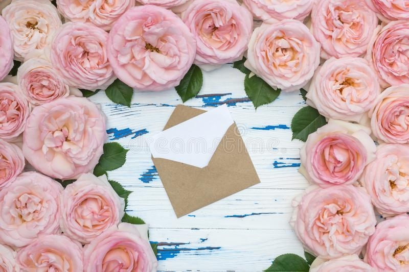 Flowers composition. Open envelope in the frame made of pink roses on aged wooden background. Flat lay, top view, copy space royalty free stock image