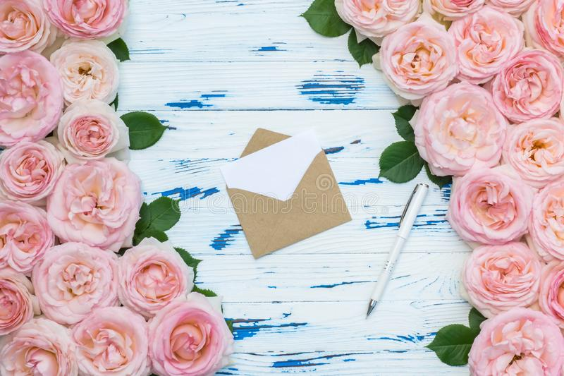 Flowers composition. Open envelope and pen in the frame made of pink roses on aged white wooden background. Flat lay, top view, copy space stock image