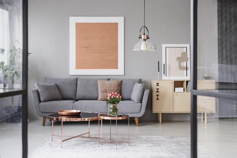 Flowers on copper table in front of grey couch in living room interior with rose gold poster. Real photo stock images