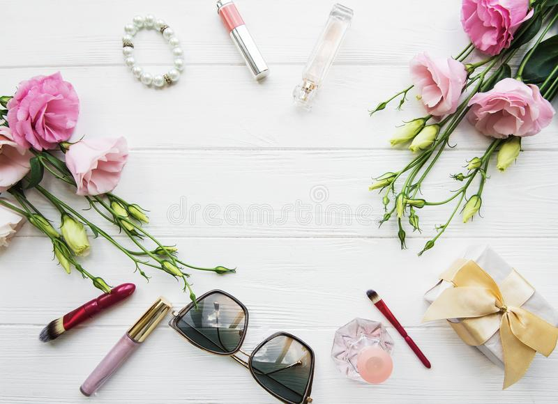 Flowers and cosmetics. On a white wooden table, flat lay royalty free stock images