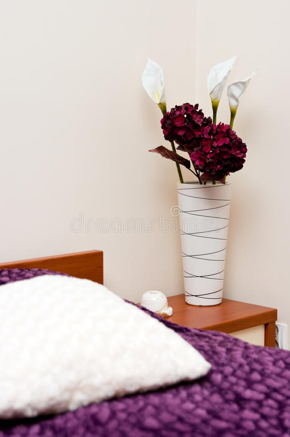 Flowers in cosy bedroom. Decorative flowers on bedside table in cosy modern bedroom royalty free stock photography