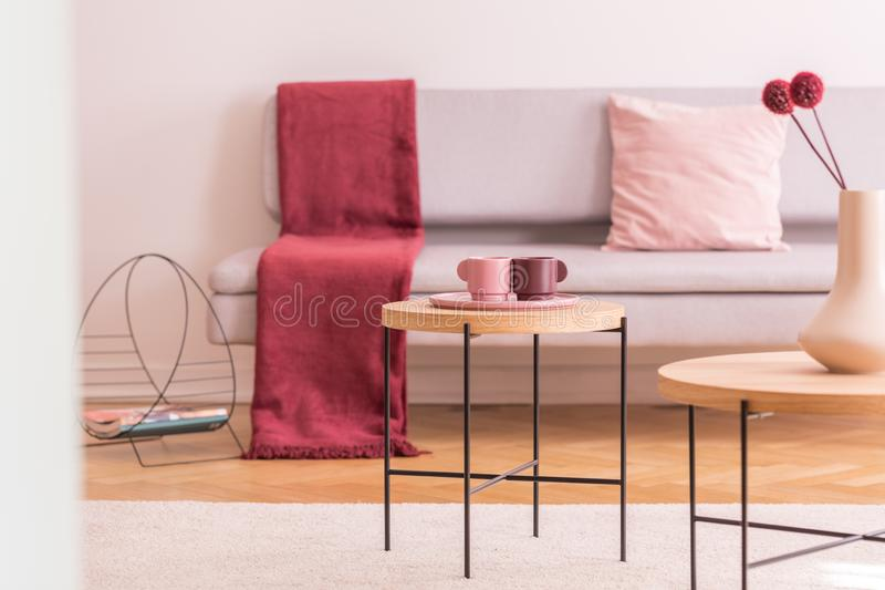 Flowers and cups on wooden tables in living room interior with red blanket on grey sofa. Real photo. Concept photo royalty free stock photo