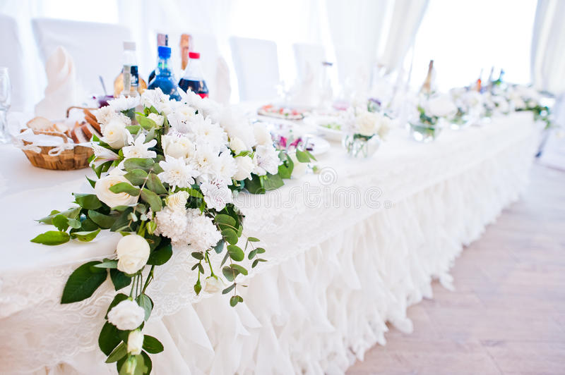 Flowers decor on table of newlyweds at wedding hall.  royalty free stock image