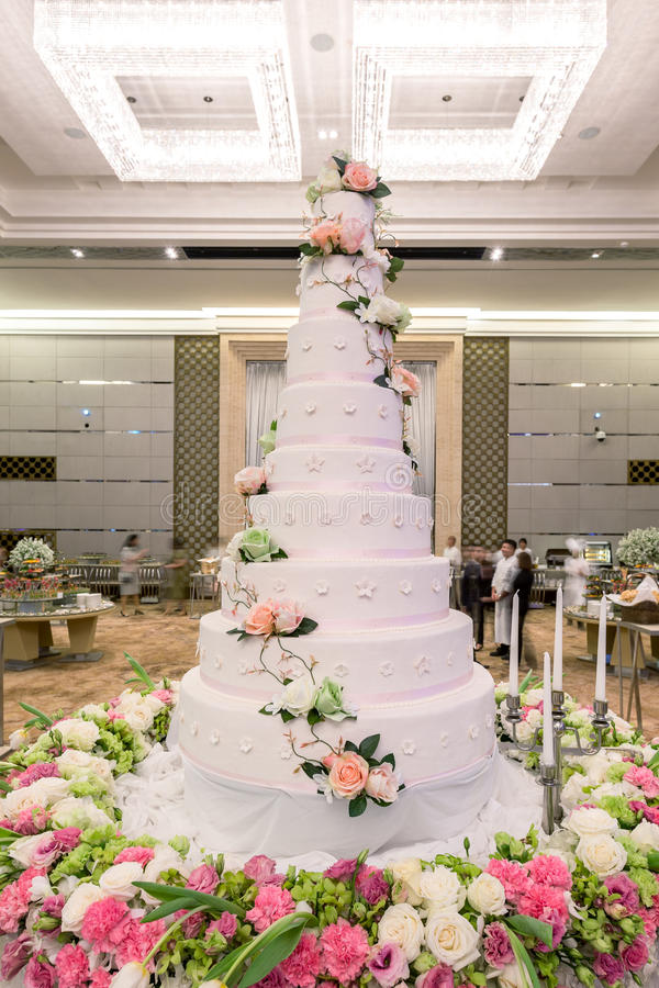 Flowers and decorations around wedding cake with chandelier on c. Eiling. - (Selective focus on wedding cake royalty free stock photography