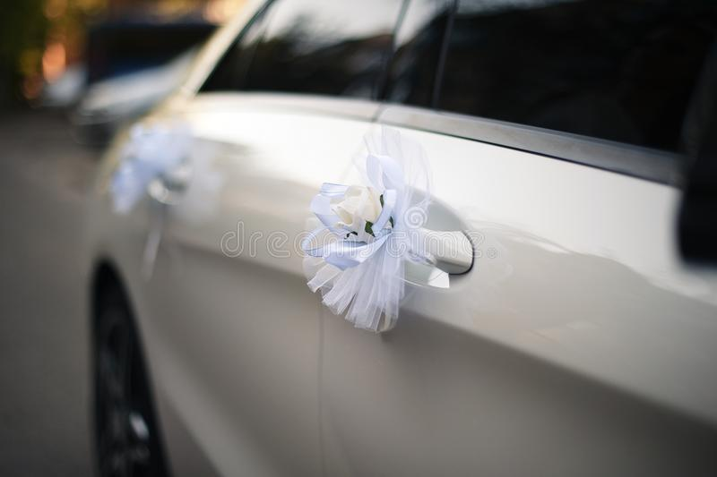 Flowers and decorations at the white wedding car royalty free stock image