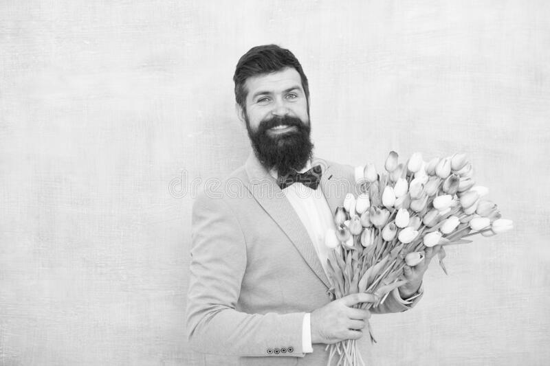 Flowers delivery. Gentleman romantic date. Birthday greetings. Best flowers for girlfriend. Flowers for her. Man bearded. Suit bow tie hold tulips bouquet royalty free stock photo
