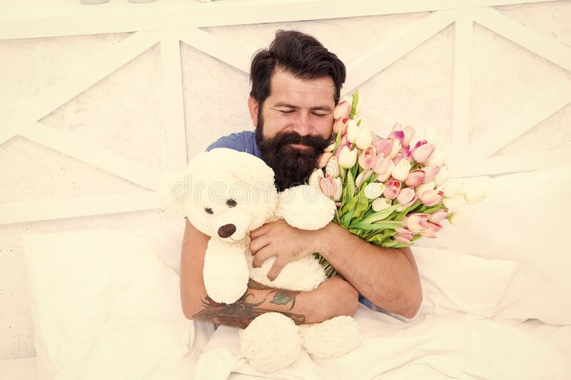 Flowers delivery service. Make surprise concept. Gift for spouse. Cute teddy bear. Fresh flowers. Bearded hipster in bed. Valentines day gift. Birthday holiday stock photography