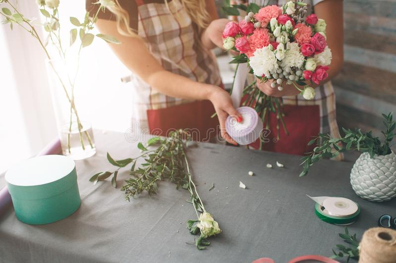 Flowers delivery top view. Florists creating order, making rose bouquet in flower shop. Two female florists are doing stock images