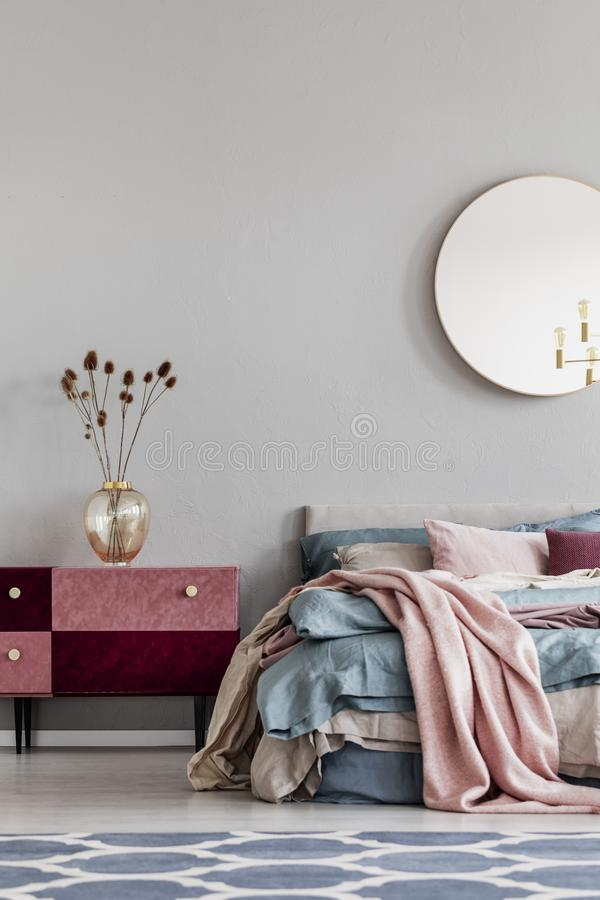 Flowers in elegant glass vase on diy velvet covered pastel pink and burgundy nightstand next to cozy bed with blue and beige royalty free stock image