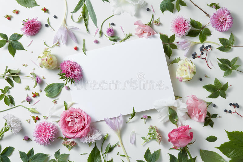 Flowers with empty white notebook. Pattern flowers with empty white notebook on a white background, copy space for your text or design royalty free stock photo