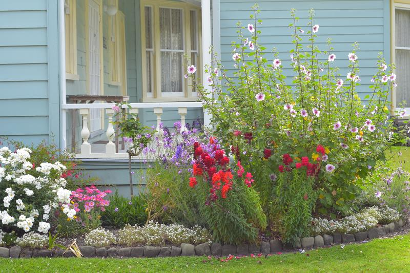 Flowers in front of wooden villa. Colorful flowers in front of classic wooden villa porch royalty free stock image