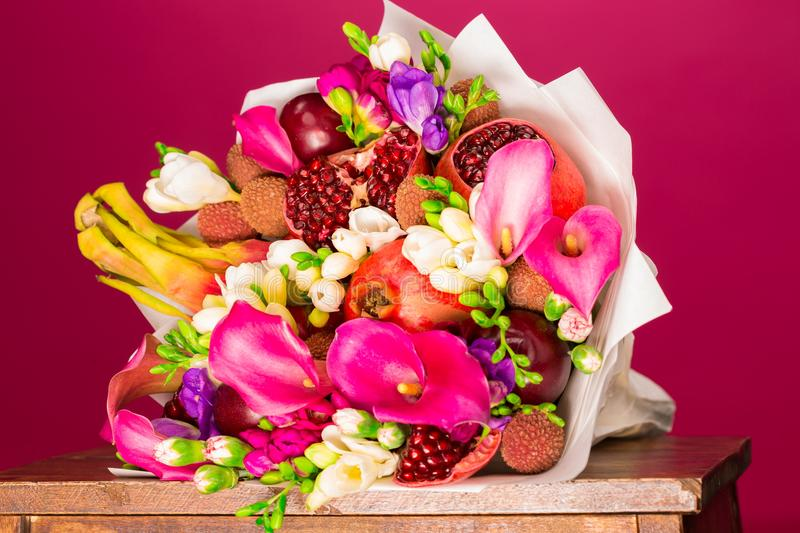 Flowers, fruit bouquet, pink callas, garnet, lychees, freesia, p. Beautiful fresh spring exotic fruit flowers tropical bouquet: pink callas, garnet, lychees stock image