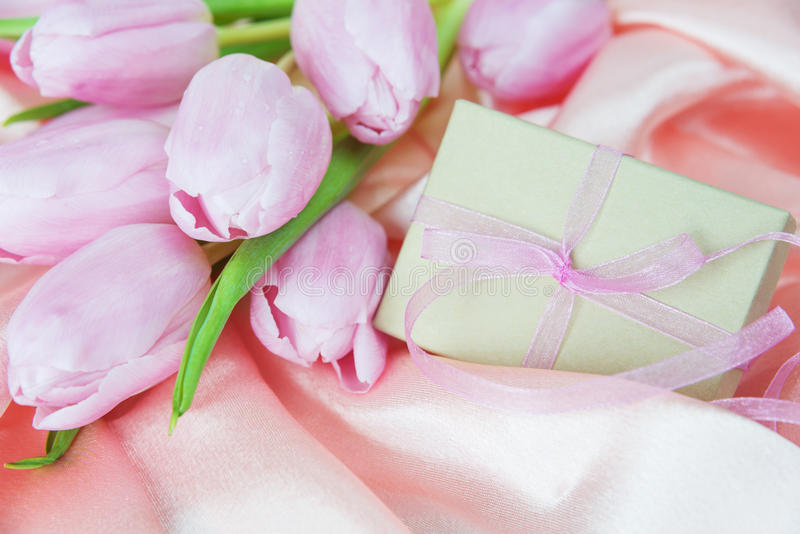 Flowers and gift box on a silk fabric stock photos