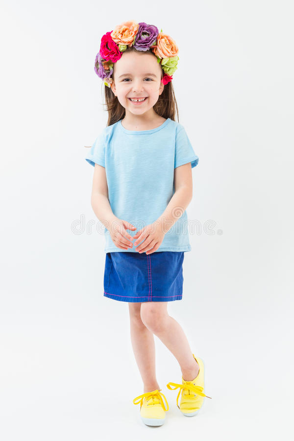 Flowers head accessory blue t-shirt navy skirt yellow sneakers casual style. No print clotes. Catalog template for branding. Smiling small kid girl. White royalty free stock photos