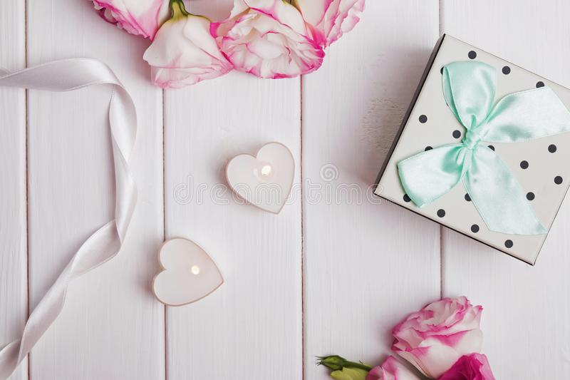 Flowers, heart shaped candles and gift box on the white wooden background. stock photos