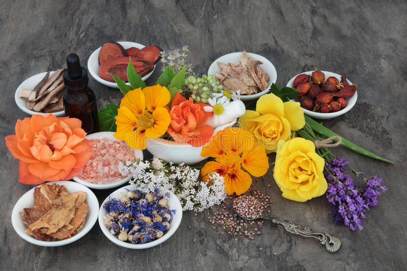 Flowers and Herbs for Natural Healing. Flower and herb selection used in natural alternative herbal medicine with essential oil bottle and mortar with pestle stock images