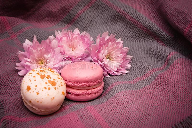 Flowers and macaroons lie on a woven tablecloth stock image