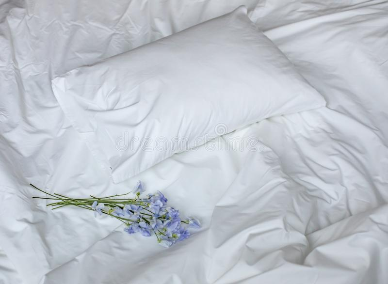 Flowers on the messy bed, white bedding items and blue flowers bouqet royalty free stock photo