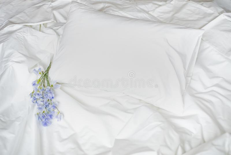 Flowers on the messy bed, white bedding items and blue flowers bouqet stock photos
