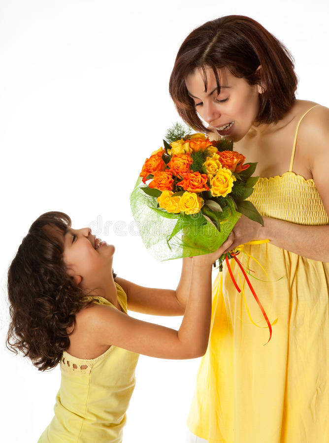 Flowers for mommy. Little girl giving flowers to mom on mother's day stock image