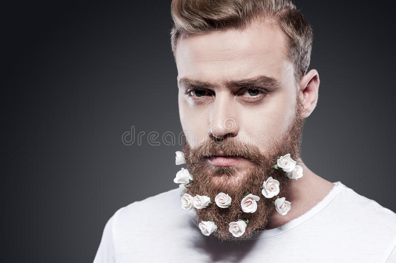 Flowers in my beard. Portrait of handsome young man with flowers in his beard looking at camera while standing against grey background royalty free stock photos