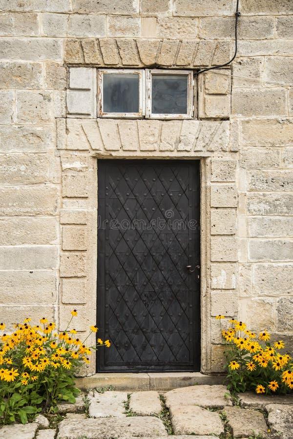 Flowers near iron door stock photography