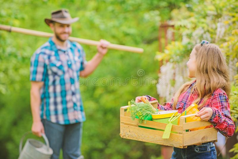 Flowers need my care. little girl and happy man dad. earth day. spring village country. family farm. ecology. Gardening. Tools. father and daughter on ranch royalty free stock photos