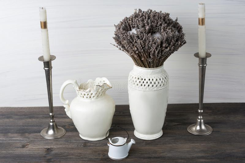 Flowers in neutral colored vases, candles on rustic wooden shelf against shabby white wall. Home decor royalty free stock image