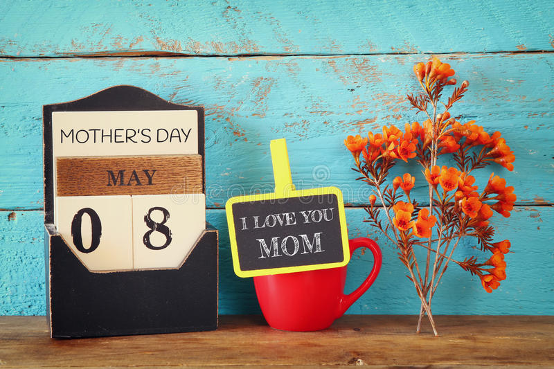 Flowers next to blackboard with phrase on wooden table. happy mother's day concept stock photos