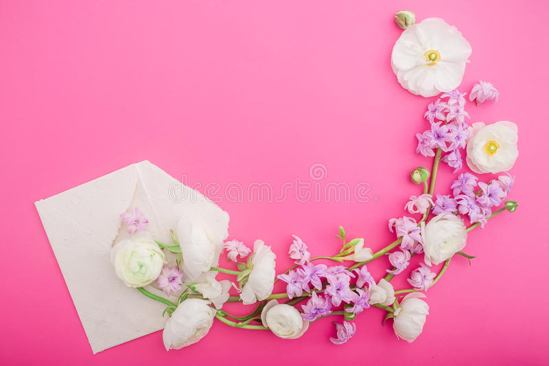 Flowers and paper envelope on pink background. Flat lay, top view. Floral round frame. Floral round frame. Flowers and paper envelope on pink background. Flat royalty free stock images